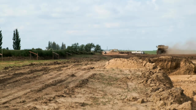 construction of highway through agricultural landscape with excavator and trucks