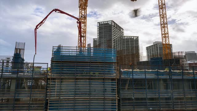 Construction of skyscraper slip forming core pillars with workers setting ribs helped by crane and pouring cement from pump aerial time lapse