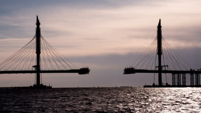 Construction of the Cable-Stayed Bridge Construction of a large cable-stayed bridge against the backdrop of the sea bay at sunset suspension bridge stock videos & royalty-free footage