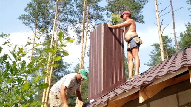 Construction of the roof. Roofers work on the roof. video