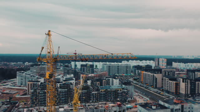 Construction powerful cranes against background of modern urban big city. The drone flies close to construction crane. Tall crane is building houses in sleeping area of the big city Construction powerful cranes against background of modern urban big city. The drone flies close to construction crane. Tall crane is building houses in sleeping area of the big city. incomplete stock videos & royalty-free footage