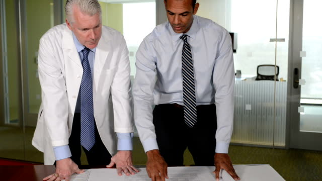 Construction Professional Discusses Blueprint Plans with Doctor video