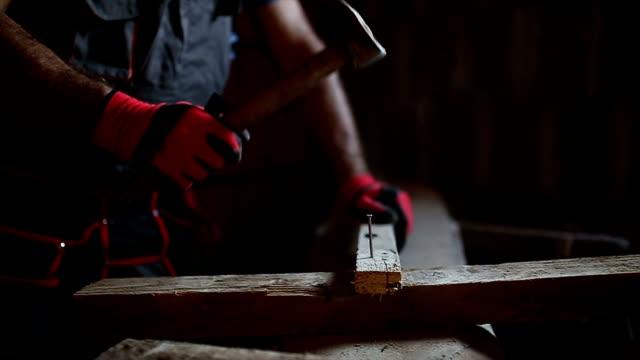 vídeos de stock, filmes e b-roll de telhador nailing construção de madeira de bordo com martelo - consertador
