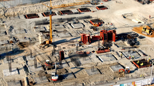 Construction site 4k timelapse. Top view of a large scale construction site with many trucks, workers and machines utilized. It is sunny day while the building's foundation are being constructed. 4k video, timelapse. foundation make up stock videos & royalty-free footage