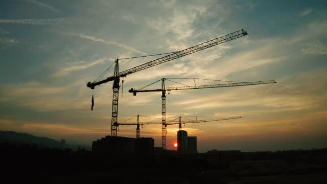 建設現場 - 夕焼け時のクレーンの空中写真 - クレーン点の映像素材/bロール