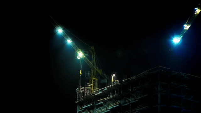 Construction site and cranes at night Two cranes with illuminated construction site at night. crane construction machinery stock videos & royalty-free footage