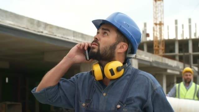 construction site foreman walking and talking on phone - operatore edile video stock e b–roll