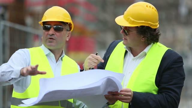Construction site manager explaining office blueprints video