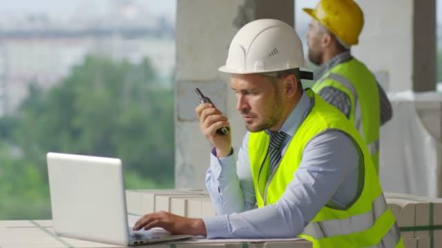 bygg arbets plats chef arbeta i ofullbordad byggnad - kommunikationssätt bildbanksvideor och videomaterial från bakom kulisserna