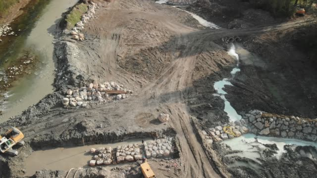 Construction site of new dam by the river side Aerial view of dam being reconstructed, shoot with a drone. Constructing a new dam with the help of construction machinery. Digging the pit with excavator. crane construction machinery stock videos & royalty-free footage