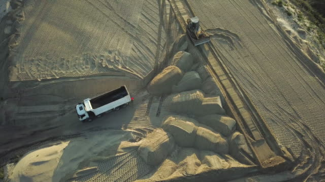 Construction site on the road construction site. Dump trucks with sand unload cargo at the construction site on a summer evening at sunset. Aerial view Construction site on the road construction site. Dump trucks with sand unload cargo at the construction site on a summer evening at sunset. Aerial view construction vehicle stock videos & royalty-free footage