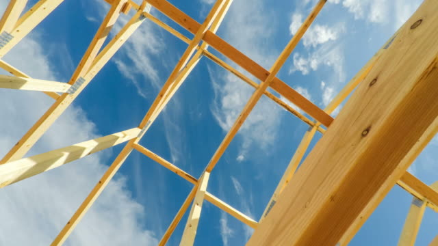 construction site roof beams under sunny blue sky - intelaiatura video stock e b–roll