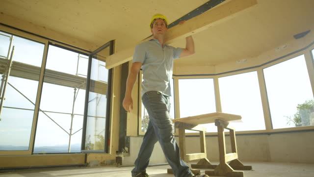 låg vinkel: byggarbetsplatsen handledare bär en logg över prefabricerade hus - solar panel bildbanksvideor och videomaterial från bakom kulisserna