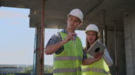 istock Construction site Team or architect and builder or worker with helmets discuss on a scaffold construction plan or blueprint or checklist. 1164758715