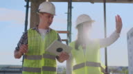 istock Construction site Team or architect and builder or worker with helmets discuss on a scaffold construction plan or blueprint or checklist. 1164760585