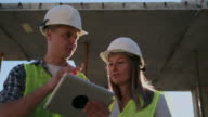 istock Construction site Team or architect and builder or worker with helmets discuss on a scaffold construction plan or blueprint or checklist. 1164763485