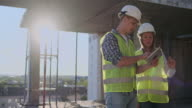 istock Construction site Team or architect and builder or worker with helmets discuss on a scaffold construction plan or blueprint or checklist. 1164764616
