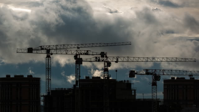 Construction site with cranes and dramatic sky