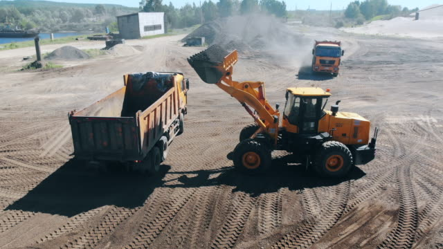 Construction site with rubble getting relocated by vehicles. Mining equipment at quarry.
