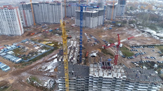 A construction site with several buildings and moving trucks. video