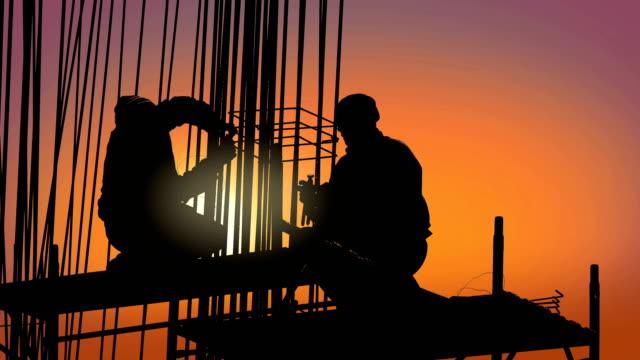 vidéos et rushes de travailleurs de la construction site construire des gratte-ciel au coucher du soleil - chantier