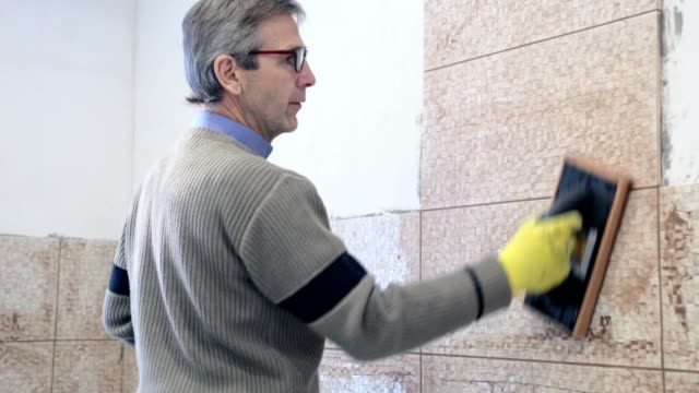 construction work with ceramic tiles. - piastrella video stock e b–roll