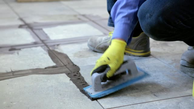 Construction work with floor ceramic tiles. The builder processes the joints between the ceramic tiles. tile stock videos & royalty-free footage