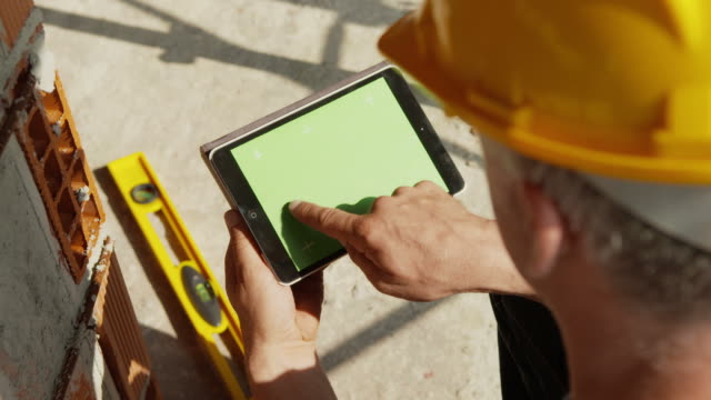 Construction worker and new house, man using digital tablet pc video