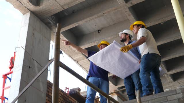 vidéos et rushes de ouvrier du bâtiment, architecte et ingénieur parlant sur le chantier et en regardant un plan tout en pointant loin - chantier