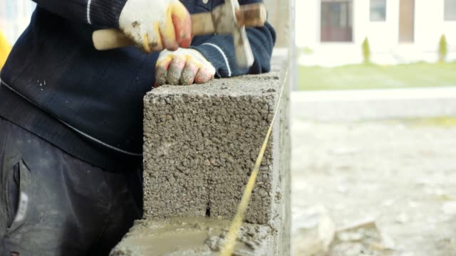 Construction worker builds brick wall, closeup view at construction site video