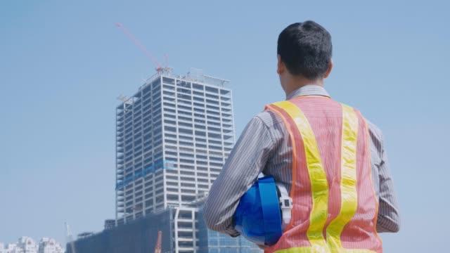stockvideo's en b-roll-footage met bouwvakker controleren van locatie site met kraan op de achtergrond - oost azië