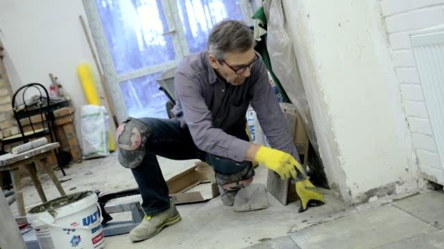 construction worker checks the installation of ceramic tiles. - качество стоковые видео и кадры b-roll