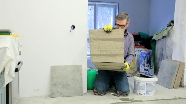 construction worker chooses a ceramic tile. - piastrella video stock e b–roll