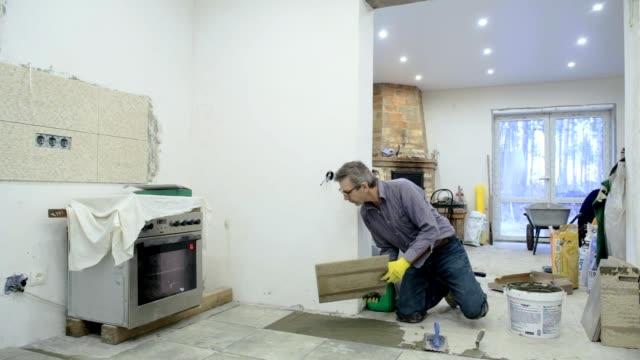 byggnadsarbetare väljer och sätter klinker på golvet. - construction workwear floor bildbanksvideor och videomaterial från bakom kulisserna