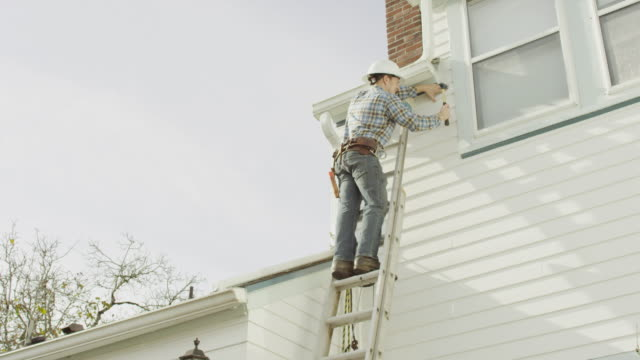 construction worker climbing up a ladder and doing work on a residential home - imprenditore edile video stock e b–roll