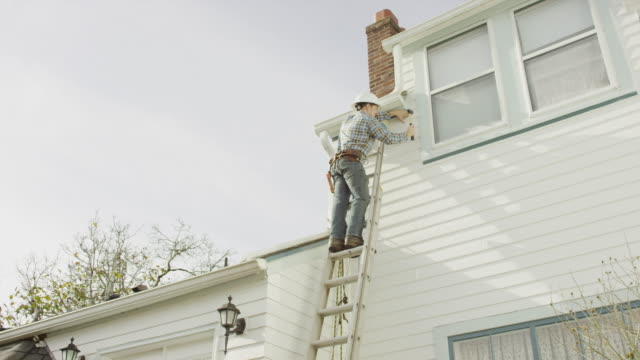 Construction worker climbing up a ladder and doing work on a residential home video