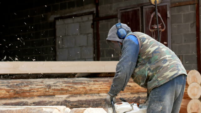 construction worker cuts wood chainsaw for future home. protective mask and headphones on the head of the builder and a lot of sawdust. hangar with a part of the future home on the background - motosega video stock e b–roll