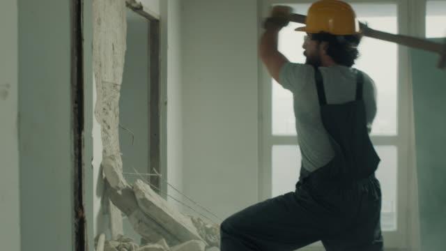 bauarbeiter demoliert mauer mit vorschlaghammer - abbrechen stock-videos und b-roll-filmmaterial