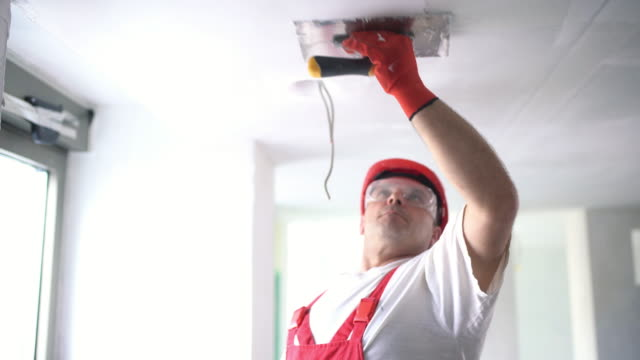 construction worker finishing a ceiling. - soffitto video stock e b–roll