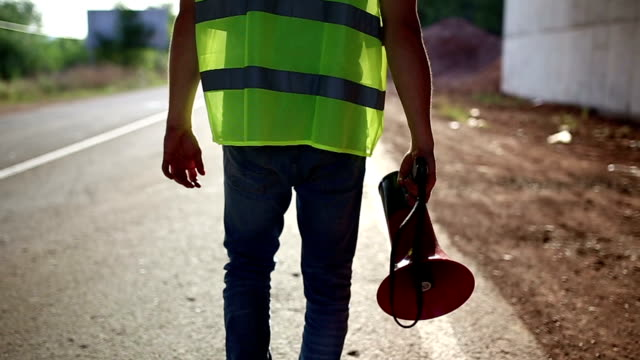 Construction worker holding megaphone,walking away,rear view Construction worker holding megaphone,walking towards camera megaphone stock videos & royalty-free footage