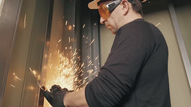 A construction worker in a helmet and glasses works with an angle grinder. A construction worker in a helmet and glasses works with an angle grinder. 4k video. Repair and construction of the house. craftsman architecture stock videos & royalty-free footage