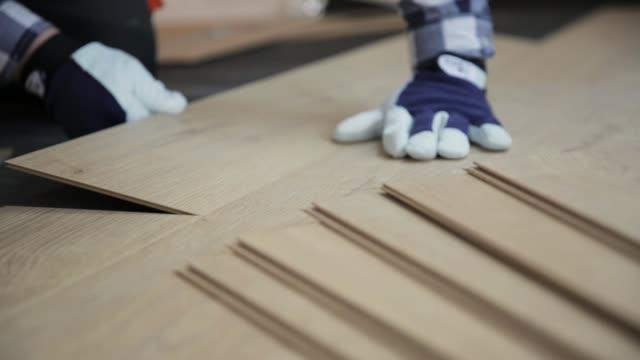 byggnadsarbetare installerar laminatgolv på en ny renoverad vind. hem förbättring koncept - golv bildbanksvideor och videomaterial från bakom kulisserna