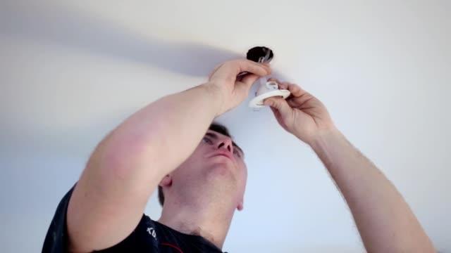 Trabajador de la construcción instala una lámpara en el techo. - vídeo
