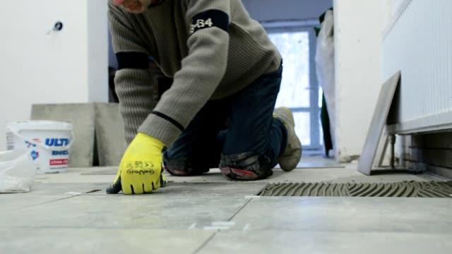 byggnadsarbetare installerar keramiska plattor. - construction workwear floor bildbanksvideor och videomaterial från bakom kulisserna