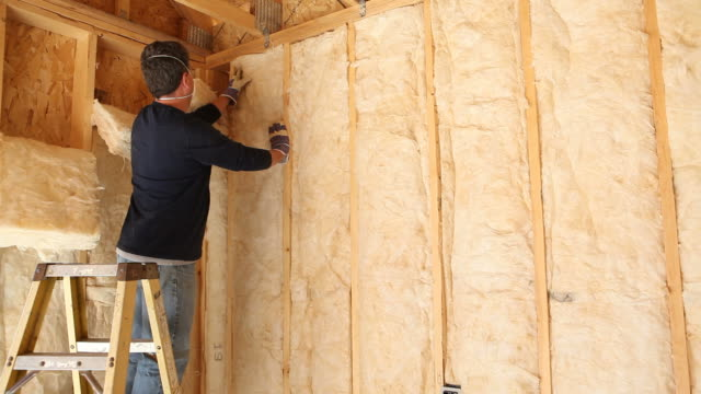 Construction Worker Insulating Wall with Fiberglass Batt video