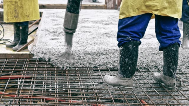 construction worker moving the hose to pour concrete into the openings in the rebar mesh - spranga video stock e b–roll