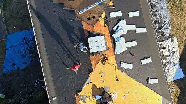 vídeos y material grabado en eventos de stock de trabajador de la construcción en un techo de renovación de la casa instaló tejas nuevas - material de construcción