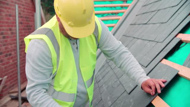 byggnadsarbetare på byggnadsplatsen lägga skiffer plattor - yttertak bildbanksvideor och videomaterial från bakom kulisserna