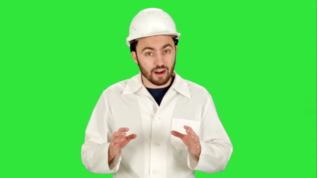 Construction worker on building site talking to camera on a Green Screen, Chroma Key video