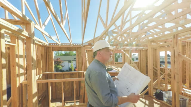 Construction Worker on Site with Building Plans